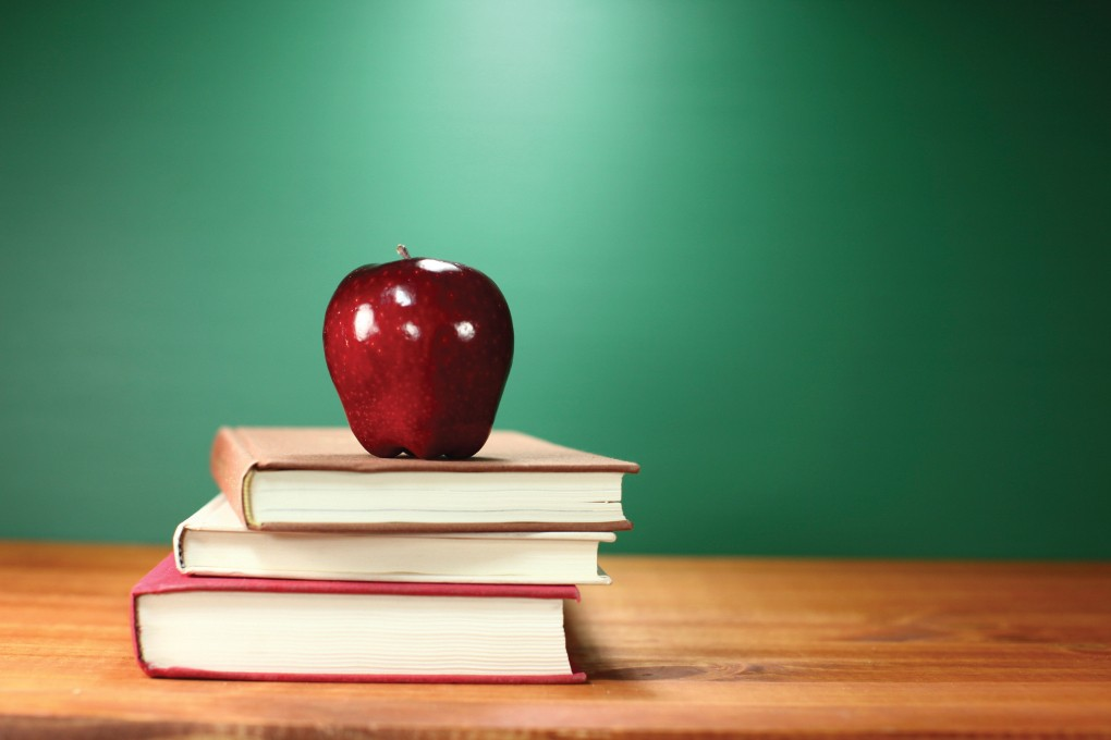 stock image of red apple on three books
