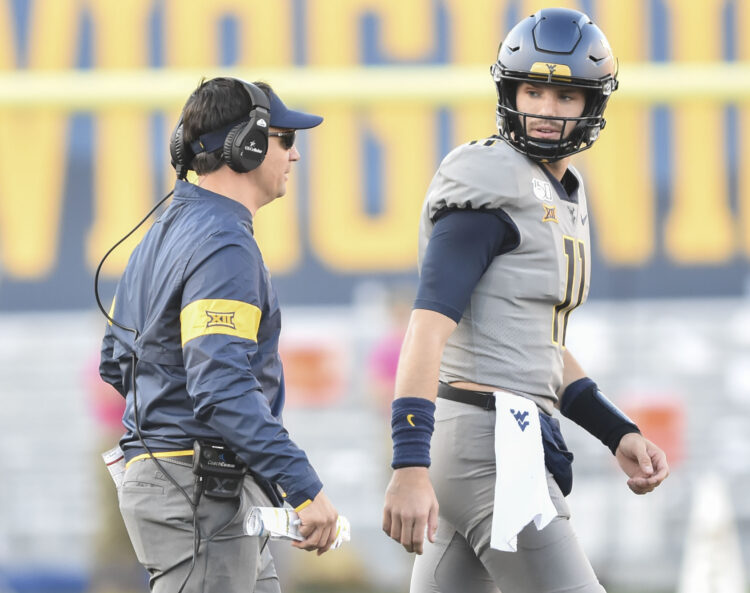 West Virginia quarterback Jack Allison talks with coach Neal Brown during the Iowa State game. (William Wotring/The Dominion Post).