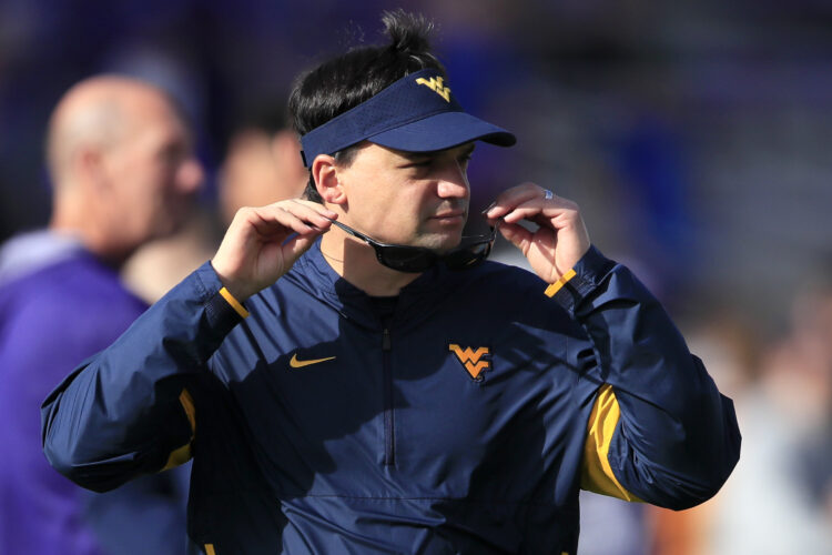 West Virginia head coach Neal Brown dons sunglasses before  Saturday's game at Kansas State (AP photo).