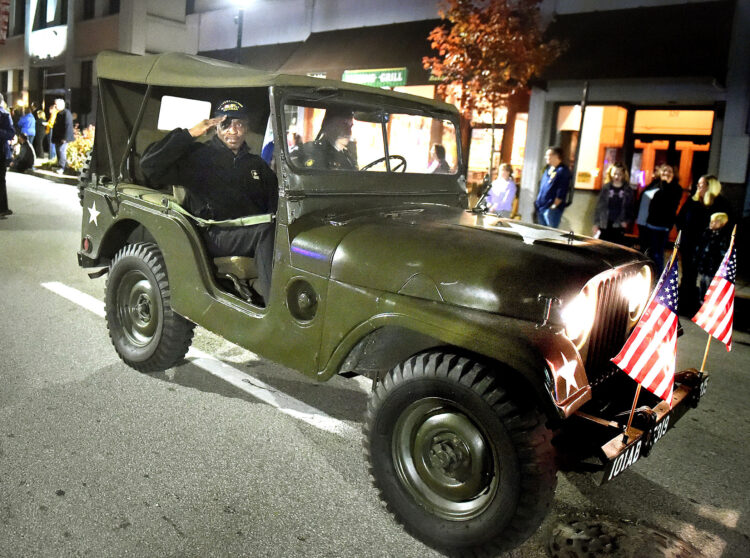 A Vietnam veteran salutes as he rides in a military jeep.