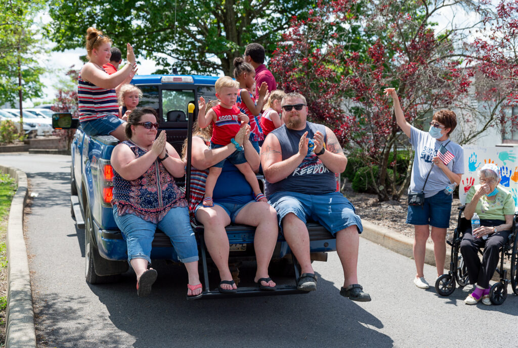 group on truckbed sings and claps as part of Sundale Memorial Day Parade
