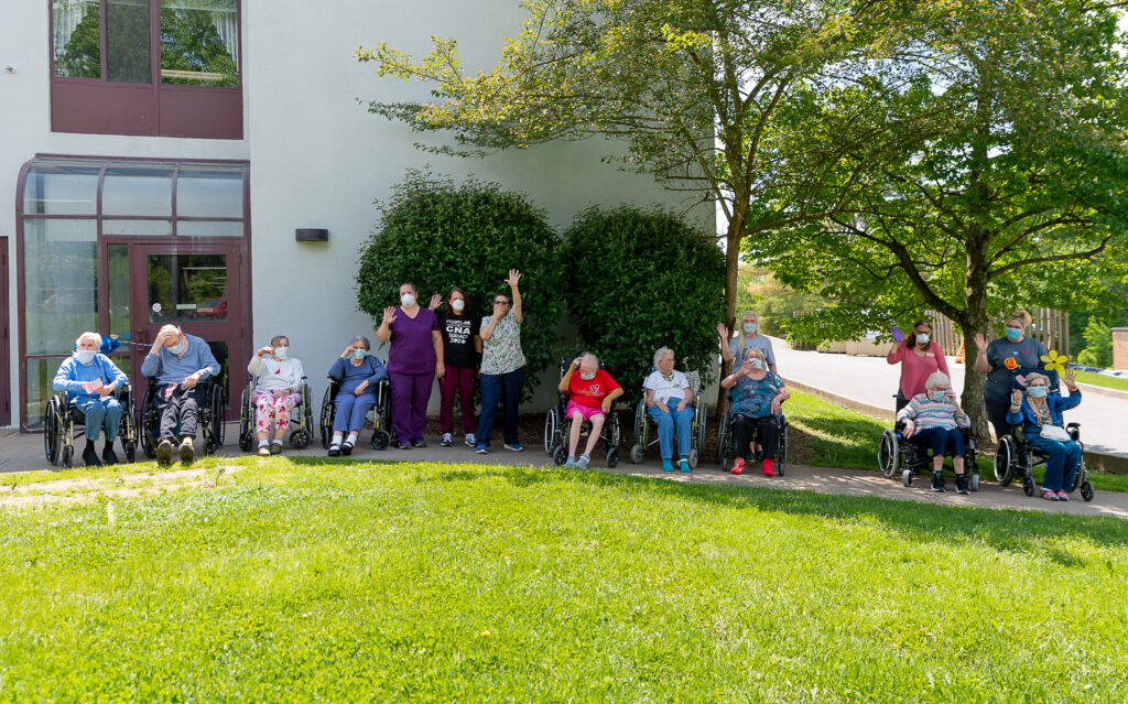 residents and staff wave to the Sundale Memorial Day parade