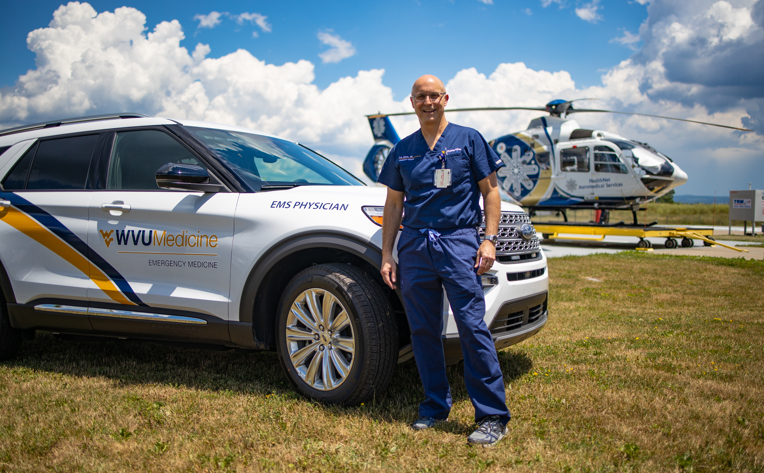 Dr. P.S. Martin in front of quick response vehicle & helicopter