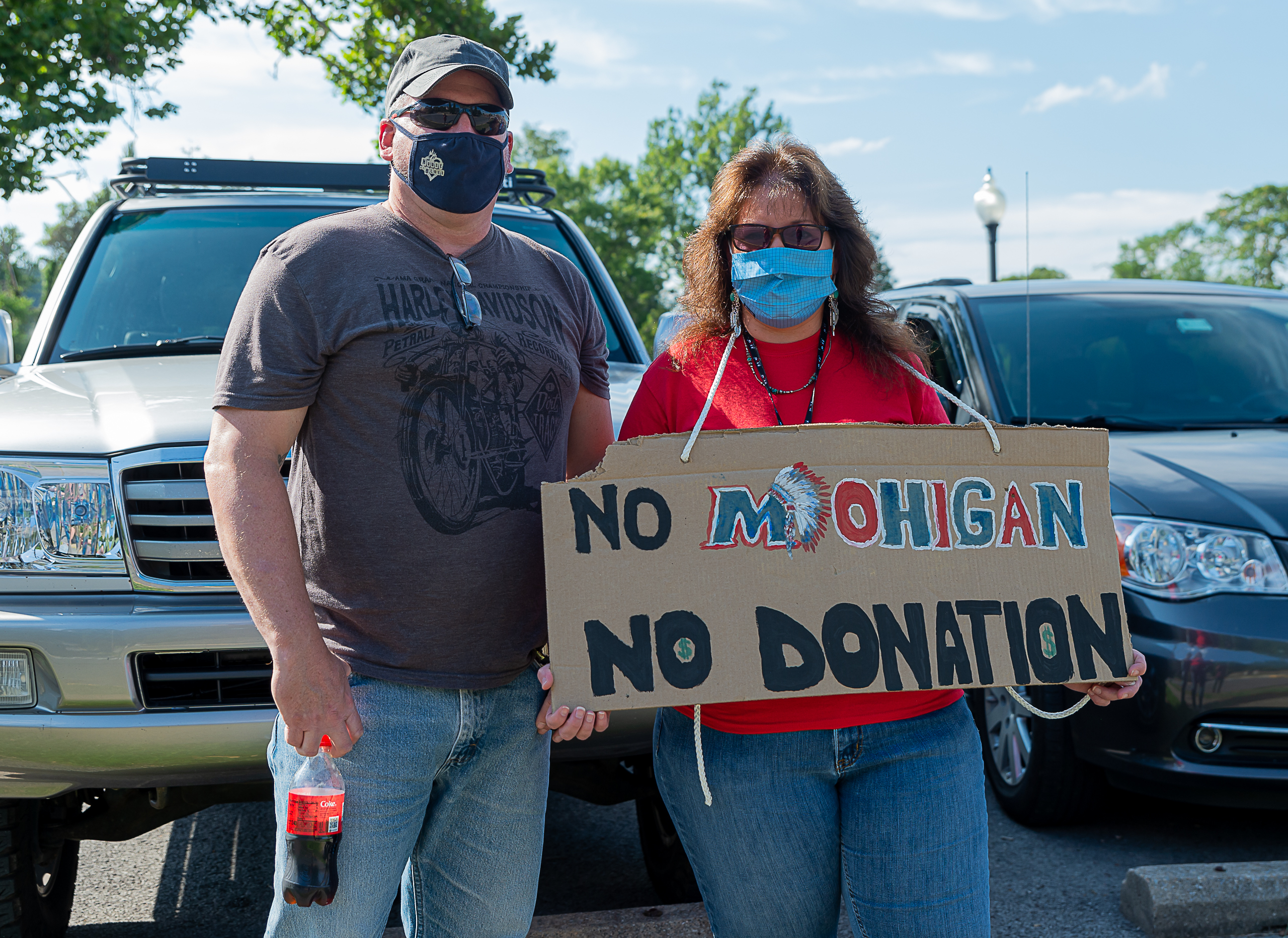 couple holds sign to save teh mohigan mascot