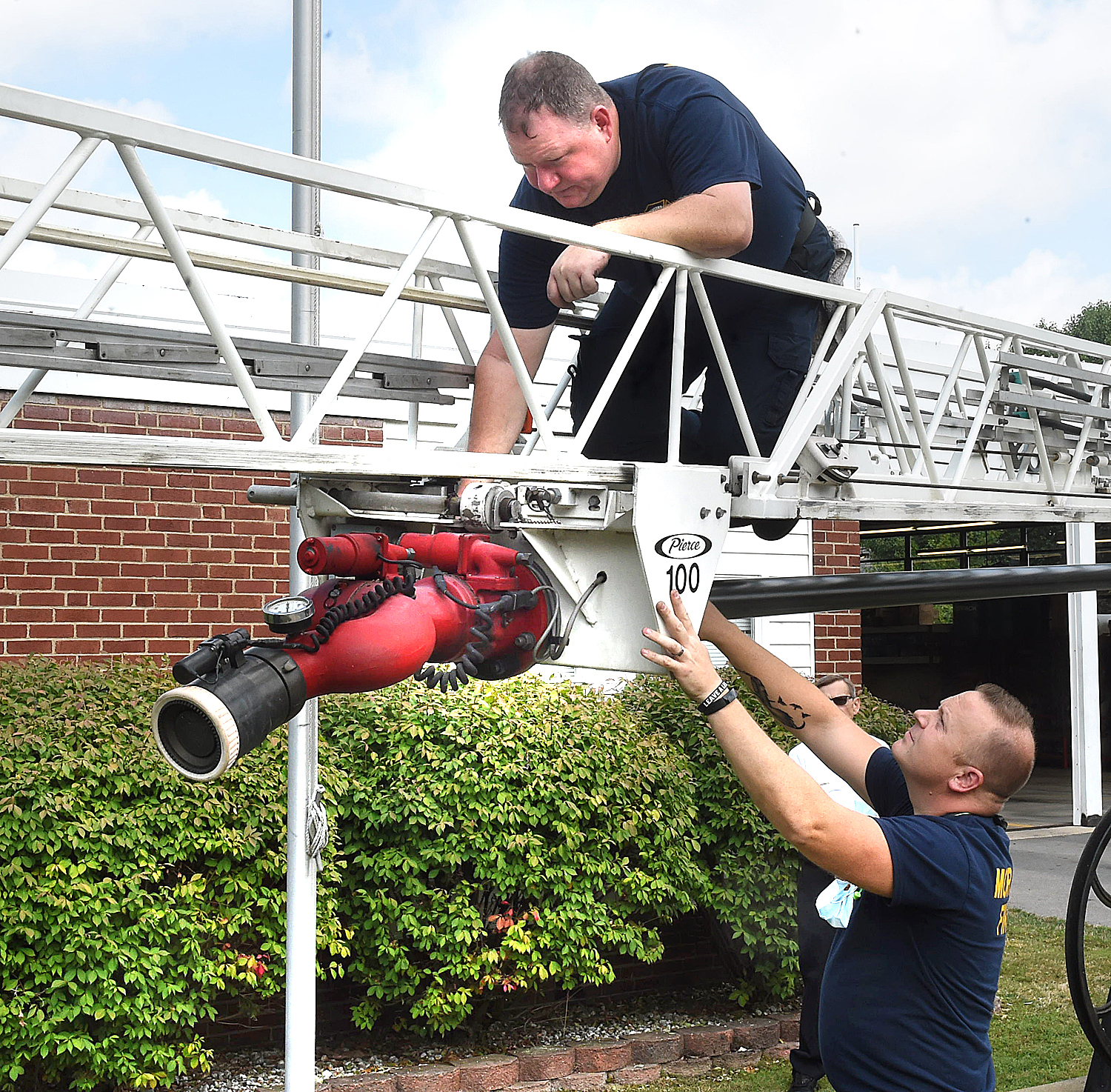 firefighters check the nozzle on extension ladder